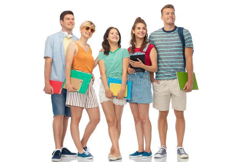 Students with notebooks, books and folders. Education and people concept - group of smiling students with notebooks, books and folders over white background stock photo