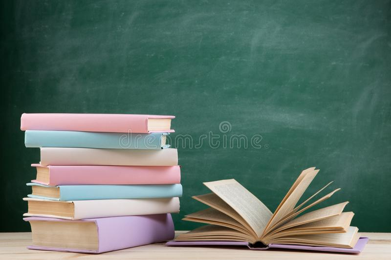 Education and reading concept - group of colorful books on the wooden table in the classroom, blackboard background. Education and reading concept - group of royalty free stock photo