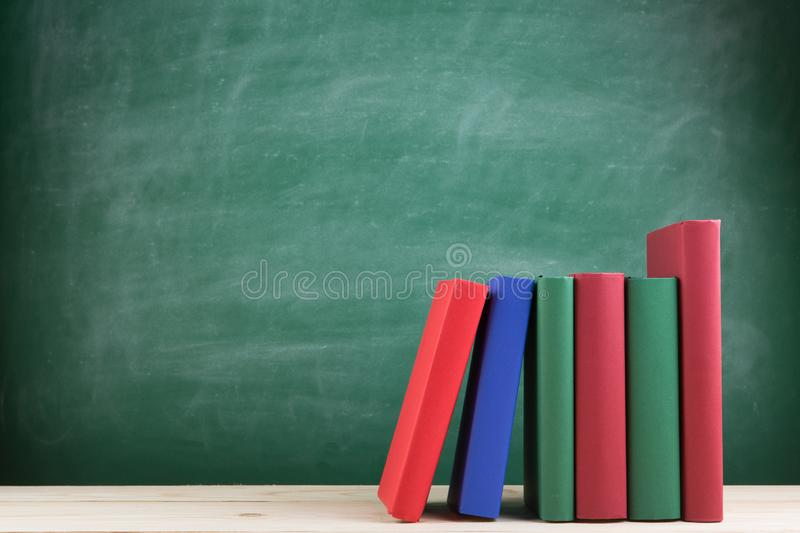 Education and reading concept - group of colorful books on the wooden table in the classroom, blackboard background. Education and reading concept - group of stock photo