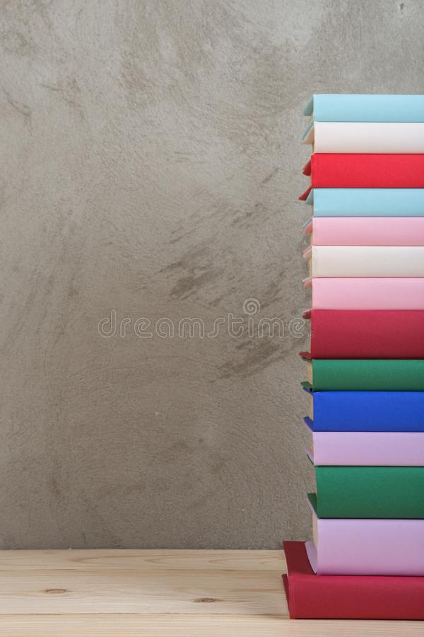 Education and reading concept - group of colorful books on the wooden table, concrete wall blackboard. Education and reading concept - group of colorful books on stock photo