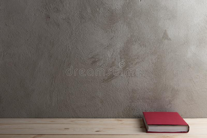 Education and reading concept - group of colorful books on the wooden table, concrete wall blackboard. Education and reading concept - group of colorful books on royalty free stock image