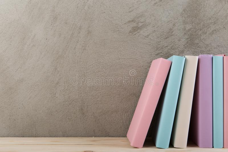 Education and reading concept - group of colorful books on the wooden table, concrete wall blackboard. Education and reading concept - group of colorful books on royalty free stock photography