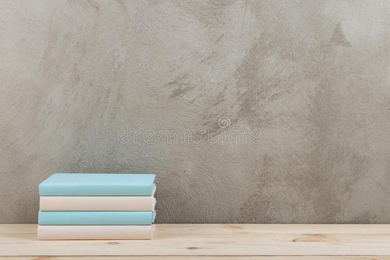 Education and reading concept - group of colorful books on the wooden table, concrete wall blackboard. Education and reading concept - group of colorful books on royalty free stock photos