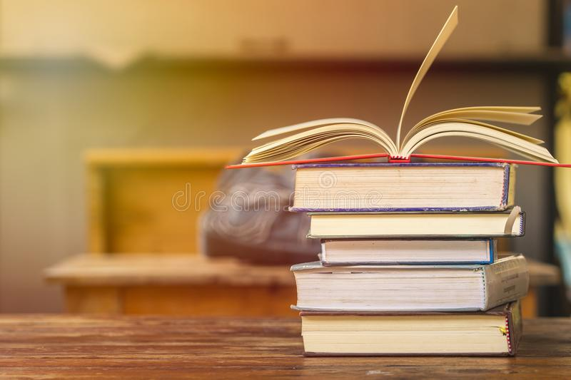 Education and reading concept - group of stack books and opened. Book on top on the wooden table with copy space for text. Home school concept. Learning at home royalty free stock images