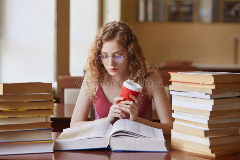Education and school concept. Clever female student girl with coffee in hand, wearing glasses and casual outfit, looks stock image
