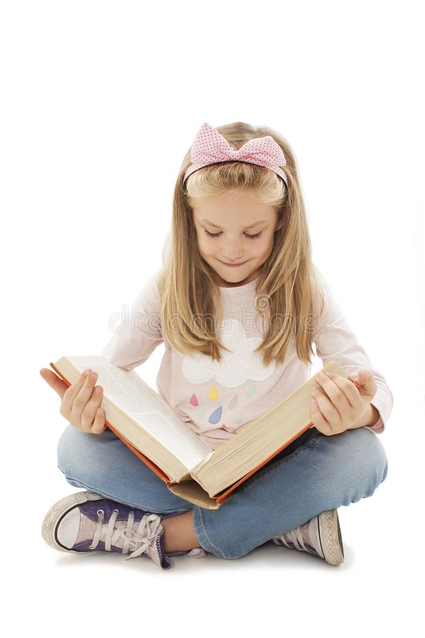 Education and school concept - little schoolgirl sitting on floor and reading book royalty free stock photos