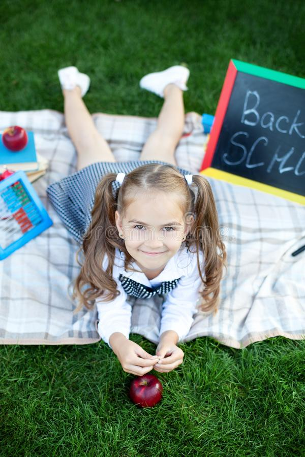 Education and school concept. Preschool education. Happy little preschool child girl with a red apple is resting in the park for l. Unch. The first day to school royalty free stock image