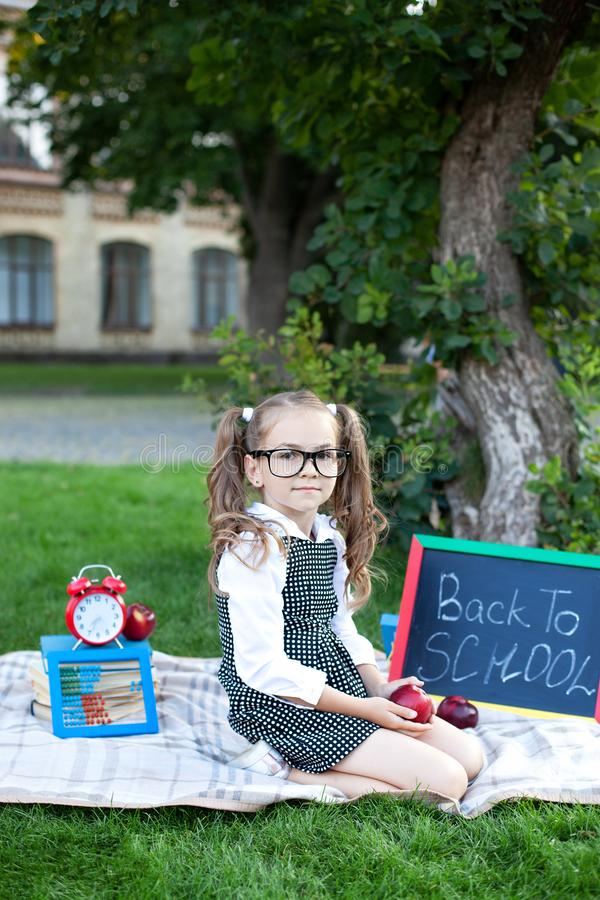 Education and school concept. Preschool education. Happy little preschool child girl with red apple sitting in the park for lunch. The first day to school or stock image