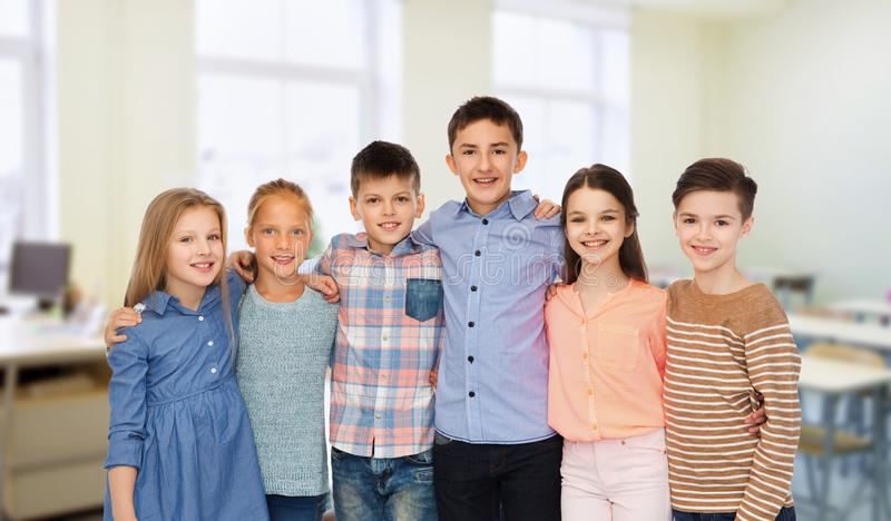 Happy students hugging at school. Education, school, friendship and people concept - happy smiling students hugging over classroom background royalty free stock images