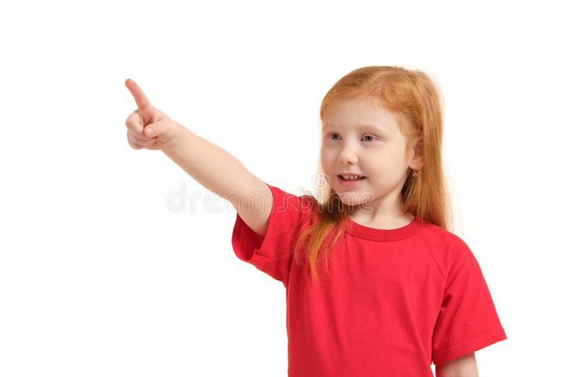 Education, school and imaginary screen concept - cute little girl pointing in the air or imaginary screen. Education, school and imaginary screen concept - cute royalty free stock image