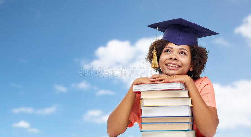 Close up of african graduate student with books. Education, school, knowledge and graduation concept - happy smiling african american graduate student girl in royalty free stock photo
