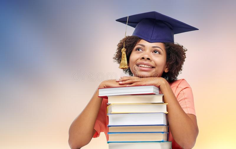 Close up of african graduate student with books. Education, school, knowledge and graduation concept - happy smiling african american graduate student girl in stock photography