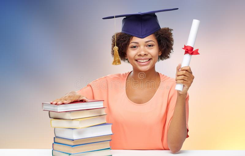 African graduate student with books and diploma. Education, school, knowledge and graduation concept - happy smiling african american graduate student girl in royalty free stock image