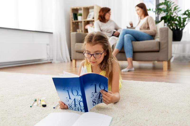 Student girl with textbook learning at home stock photography