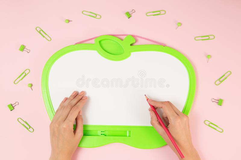 Education, school, office, social media concept. Green blackboard with copy space, clips and hand with pencil on the pink stock photography