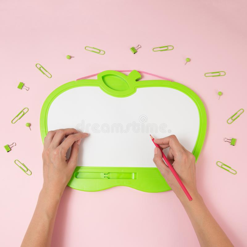 Education, school, office, social media concept. Green blackboard with copy space, clips and hand with pencil on the pink royalty free stock photo
