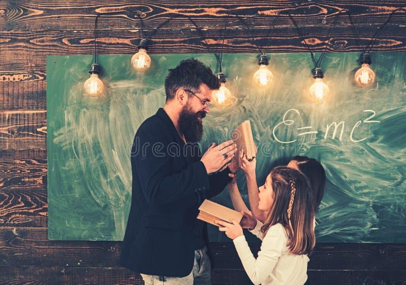 Education and school. Teacher write with chalk on chalkboard. Little girls listen to bearded man at school board. Tutor stock images