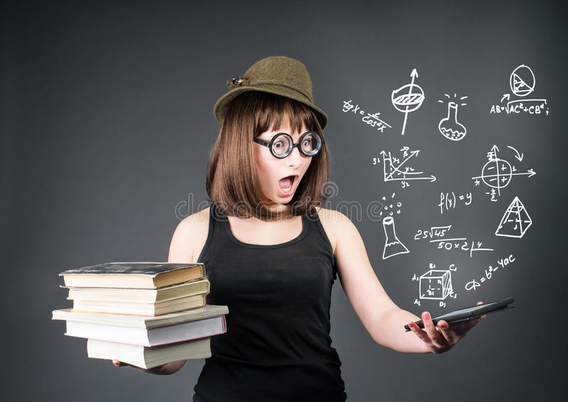 Education school technology concept. Surprised nerd student with old books in one hand and e-reader in another on grey backgro royalty free stock images