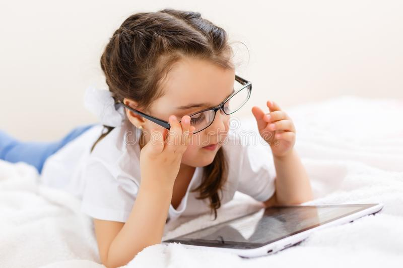 Education, school, technology and internet concept - little student girl in black eyeglasses with tablet pc computer at school stock photos