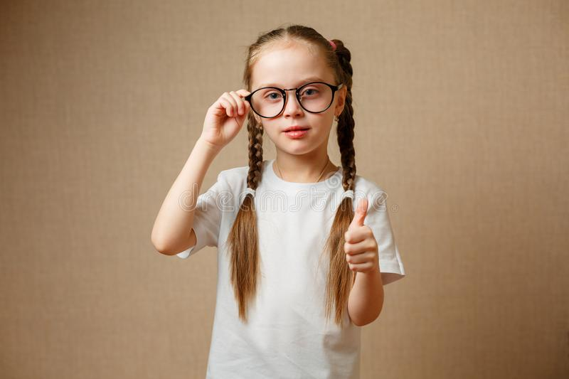 smiling cute little girl with black eyeglasses showing thumbs up stock photo