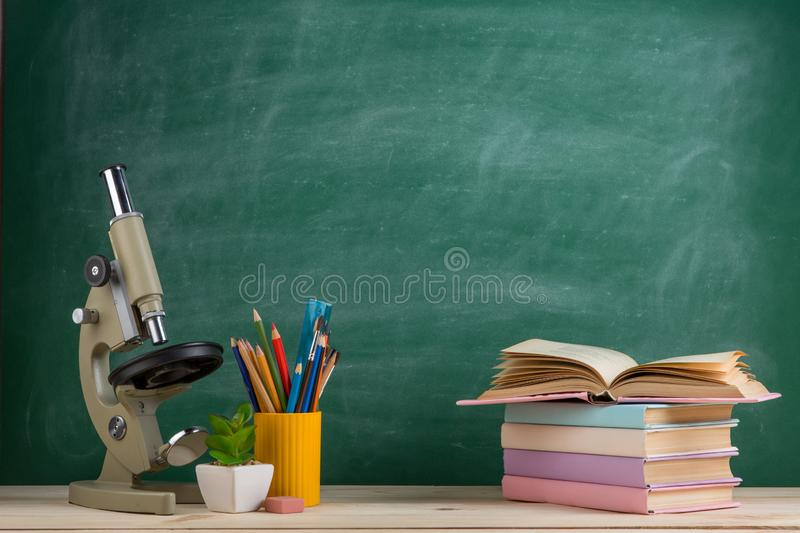 Education and science concept - group of colorful books and microscope on the wooden table in the classroom. Blackboard background, stack, school, bookshelf stock photo