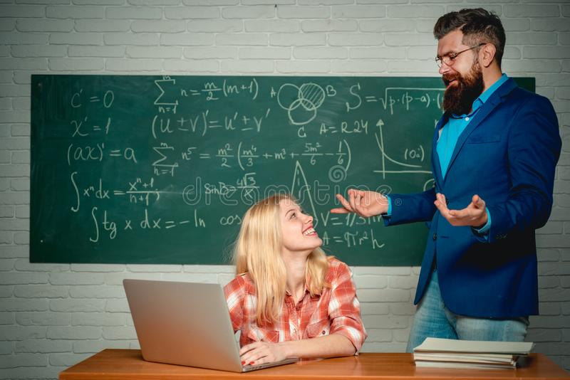 Education. Teacher helping young student with lesson. Tutoring. Student and teacher sitting at desks in classroom. University seminar. Ready for school stock image