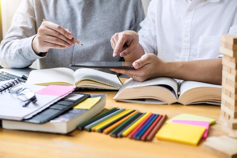 Education, teaching, learning concept. High school students or c. Lassmates group tutor in library studying and reading with helps friend doing homework and stock images