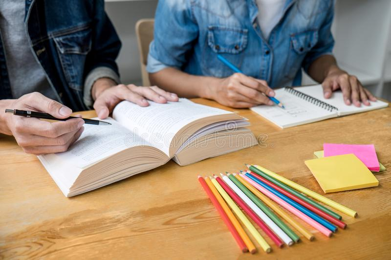 Education, teaching, learning concept. High school students or classmates group tutor in library studying and reading with helps. Friend doing homework and royalty free stock photo