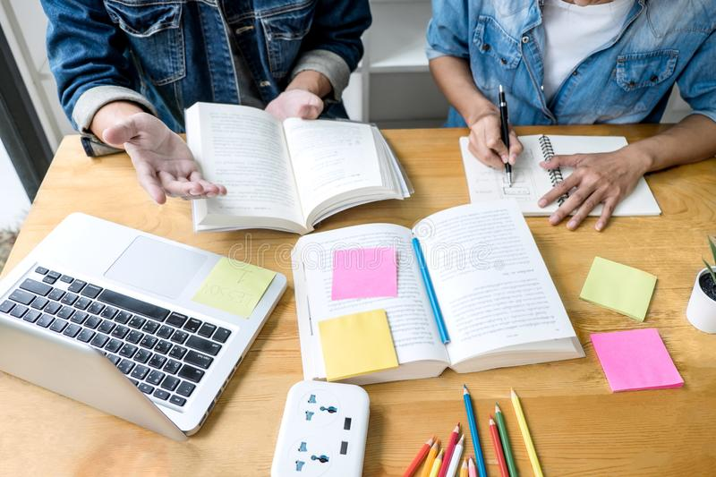 Education, teaching, learning concept. High school students or classmates group tutor in library studying and reading with helps. Friend doing homework and stock images