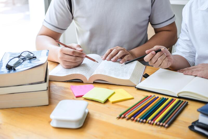 Education, teaching, learning concept. High school students or classmates group tutor in library studying and reading with helps royalty free stock photos