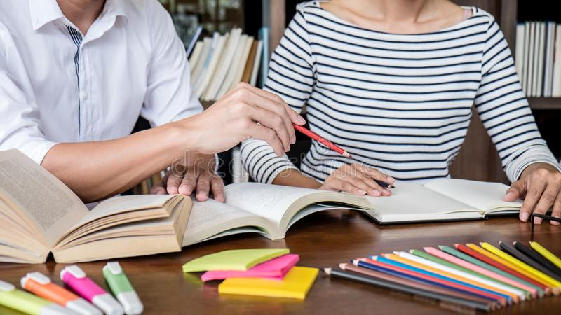 Education, teaching, learning concept. Two high school students or classmates group sitting in library with helps friend doing. Homework and lesson practice royalty free stock photography