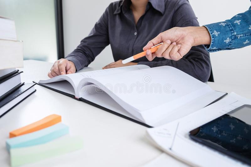 Education, teaching, learning, technology and people concept. Two high school students or classmates with helps friend catching u. P workbook learning in stock photography