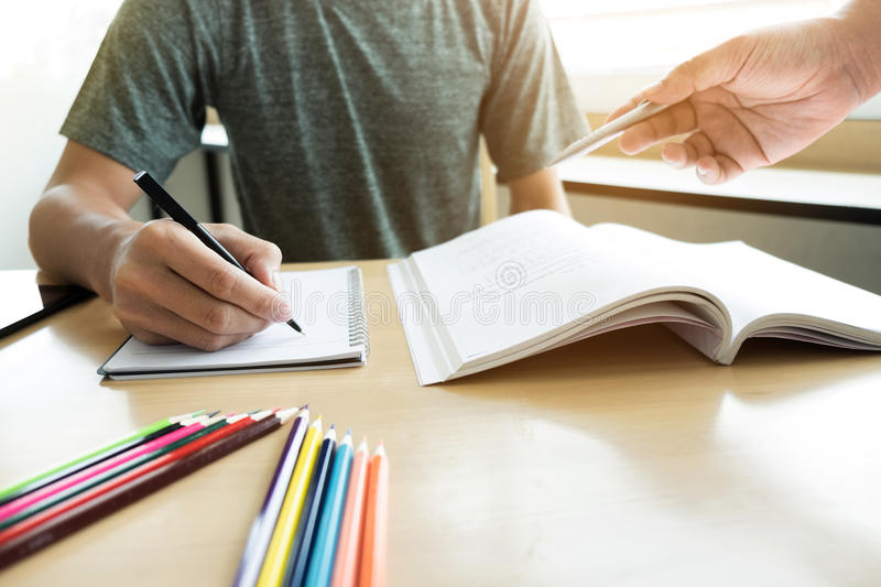 Education, teaching, learning, technology and people concept. Two high school students or classmates with helps friend catching u. P workbook learning in stock photos