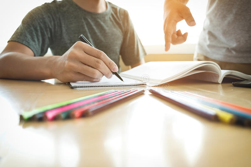 Education, teaching, learning, technology and people concept. Two high school students or classmates with helps friend catching u. P workbook learning in royalty free stock image