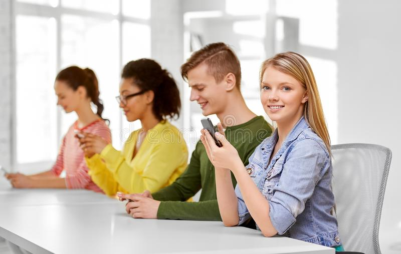 Happy high school students with smartphones stock photography