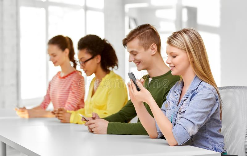 Happy high school students with smartphones royalty free stock images