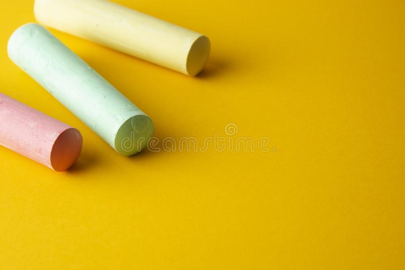 Education template. Colorful chalks over yellow background with copy space. Childhod, business and design stock photos