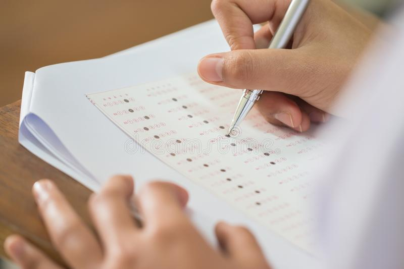 Education test concept : Blur of Hand student holding pen for testing exams writing answer sheet or exercise for taking fill in. Exam carbon paper computer on stock photo