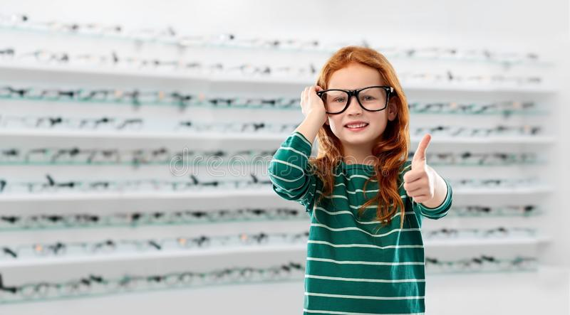 Red haired student girl in glasses at optics store royalty free stock images