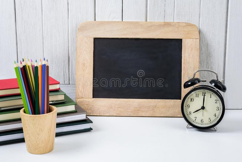 education workspace background concepts alarm clock, Color Pencil in wooden cup and Chalkboard with White wooden vintage wall royalty free stock photo