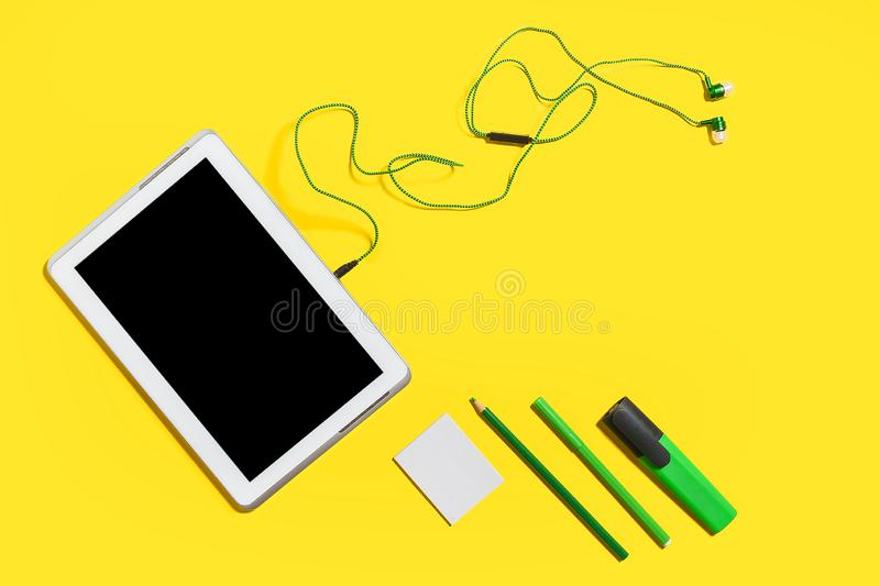 Educational accessories on a yellow surface. Set of business gadgets and accessories from the top view. green pencils, headphones, paper stickers, markers and royalty free stock image