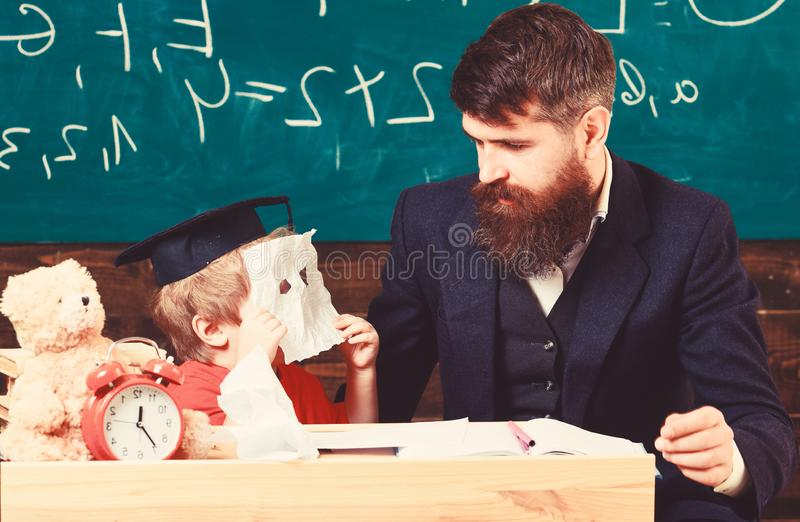 Educational concept. Handsome teacher and a small boy sitting in front of a green board. Kid in graduation cap hiding. Behind paper mask stock images