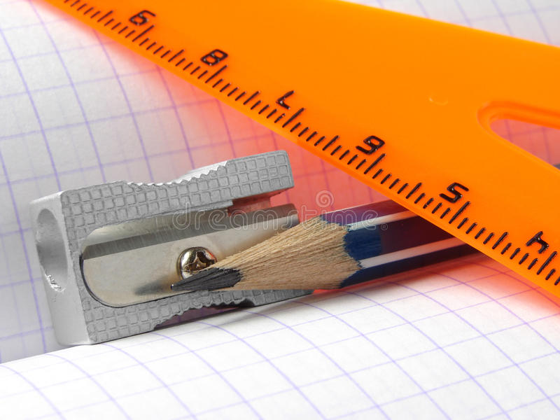 Educational set. Pencil and sharpener with triangle on the workbook page royalty free stock photos