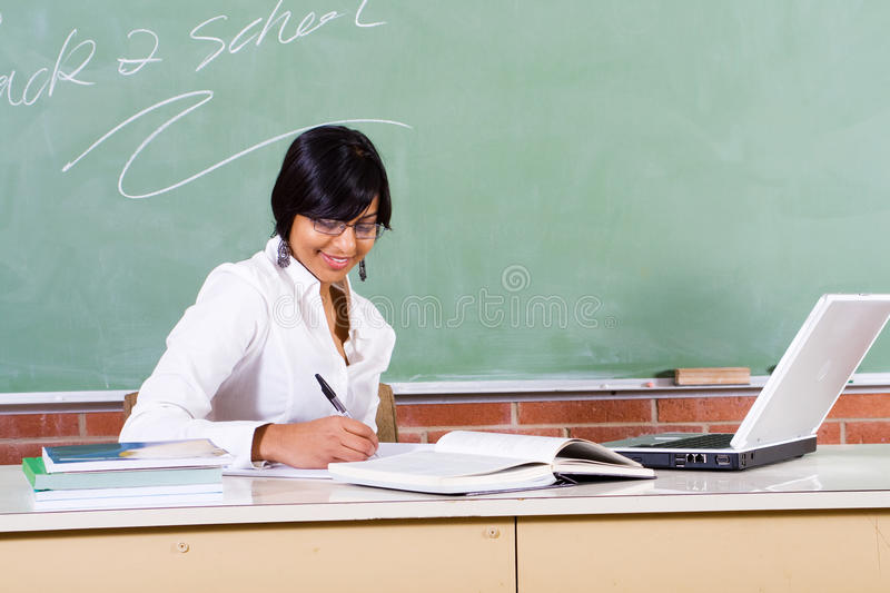 Educator. Young beautiful school educator teacher sitting in front of blackboard, back to school concept stock images