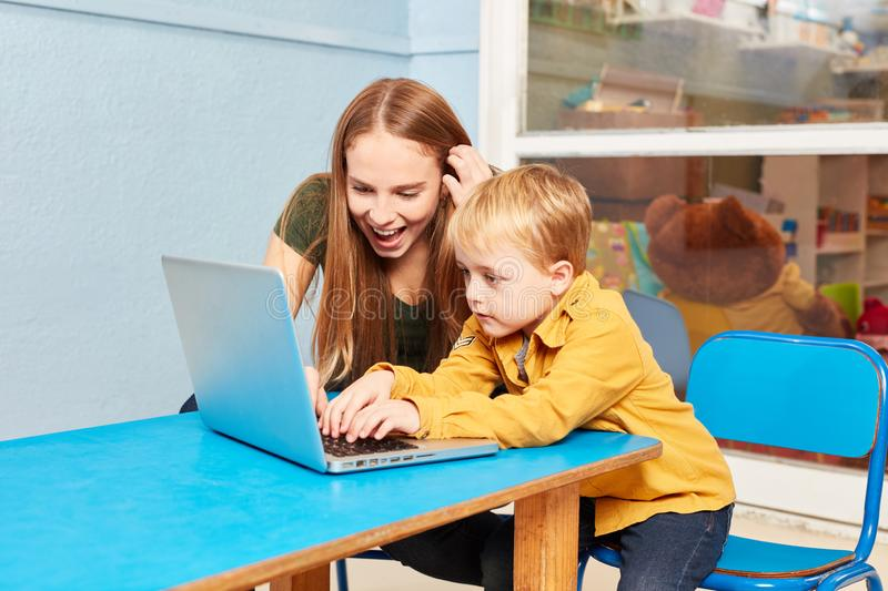 Educator and boy at laptop computer. Enthusiastic women as a teacher or educator and boy at laptop while playing computer game royalty free stock image