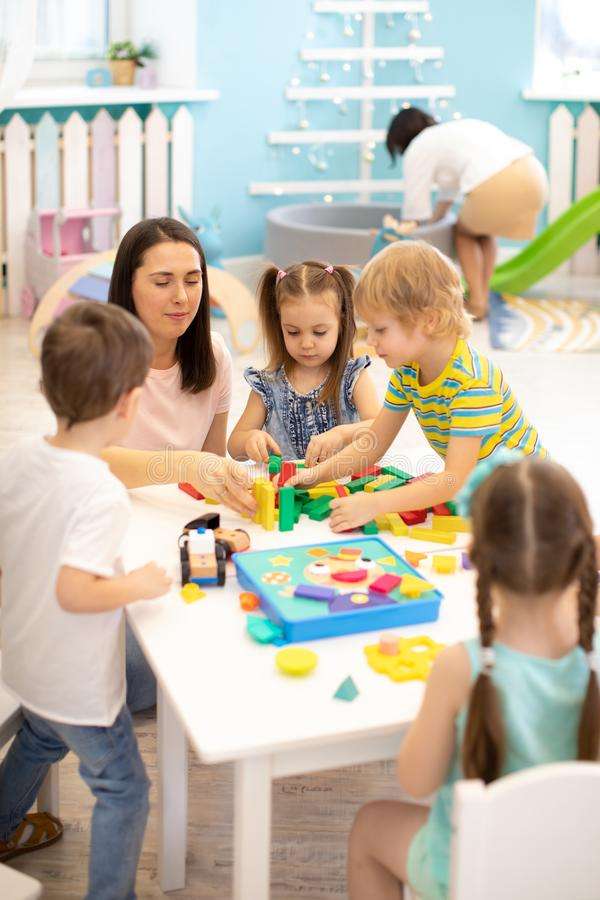 Free Educator Helping Kids Playing With Block Constructor In Daycare Royalty Free Stock Images - 144256429