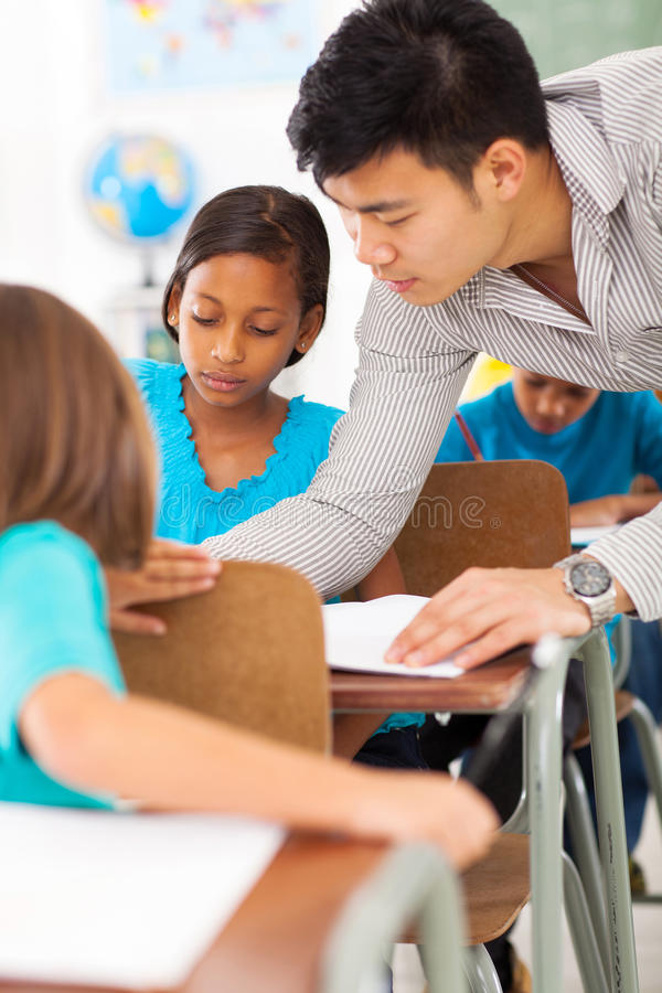 Educator helping student. Caring primary educator helping a student in classroom royalty free stock photos