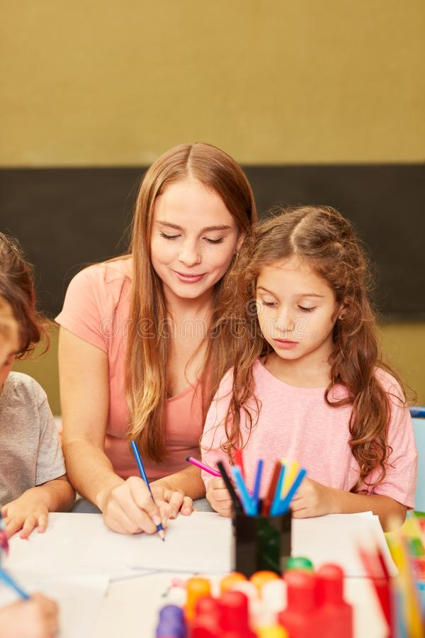 Educator helps a girl to draw. Woman as an educator helps a girl while drawing in the painting class in kindergarten royalty free stock photography