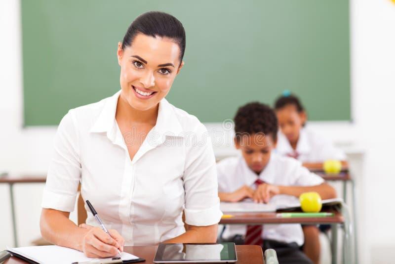 Educator preparing lessons. Attractive female school educator prepariing lessons in classroom royalty free stock images