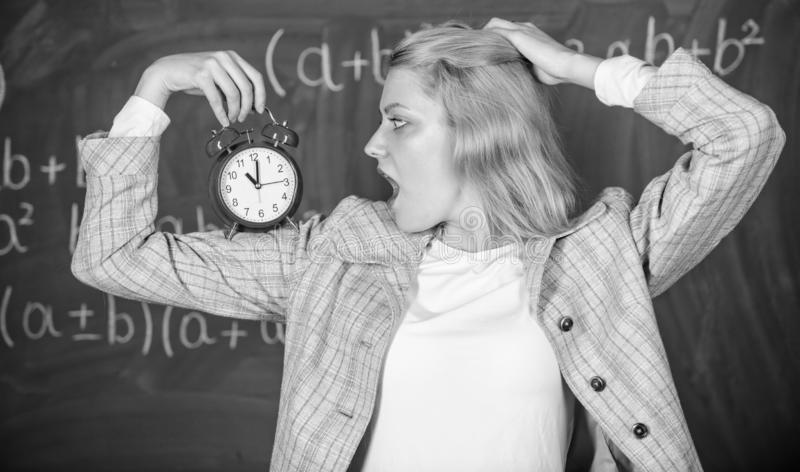 Educator start lesson. She care about discipline. Woman teacher hold alarm clock. Lessons schedule concept. Time for. Break. Girl wonder about time. Welcome royalty free stock photography